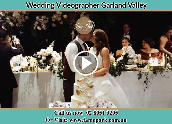The new couple kissing near the wedding cake Garland Valley NSW 2330