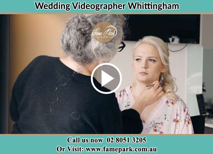 A woman applying makeup to the Bride Whittingham NSW 2330